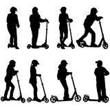 Set of silhouettes of children riding on scooters Stock Images
