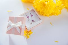 Set of silver jewellery with amethyst in the gift box with yellow flowers. Silver ring and earrings with amethyst in the gift box on wooden background stock photo