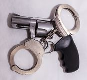 A set of silver, metal handcuffs on top of a loaded 357 magnum revolver. On a white background stock photos