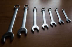Silver  metal wrenches. The Set of silver metal wrenches on a wooden background Royalty Free Stock Photos