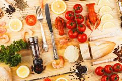 Silverware with spices, cherry tomatoes and cancers. Set from silverware, different spices, boiled cancers, cherry tomatoes, greenery and olive oil bottles on royalty free stock photo