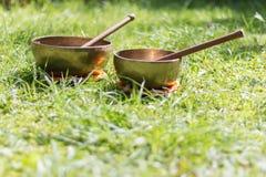 Set of singing bowls in the own garden, zen outdoors. Set of metal singing bowls in the grass of the own garden, zen wellness massage buddhism yoga alternative stock image