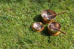 Set of singing bowls in the own garden, zen outdoors. Set of metal singing bowls in the grass of the own garden, zen wellness massage buddhism yoga alternative stock photos