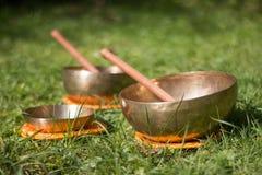 Set of singing bowls in the own garden, zen outdoors. Set of metal singing bowls in the grass of the own garden, zen wellness massage buddhism yoga alternative royalty free stock image