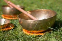 Set of singing bowls in the own garden, zen outdoors. Set of metal singing bowls in the grass of the own garden, zen wellness massage buddhism yoga alternative stock photo