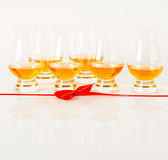 Set of single malt tasting glasses, single malt whisky in a glasses, white background, red bow. Exclusive set royalty free stock images