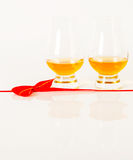 Set of single malt tasting glasses, single malt whisky in a glasses, white background, red bow. Exclusive set royalty free stock photography