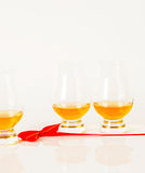 Set of single malt tasting glasses, single malt whisky in a glasses, white background, red bow. Exclusive set stock image