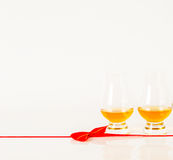 Set of single malt tasting glasses, single malt whisky in a glasses, white background, red bow. Exclusive set royalty free stock image
