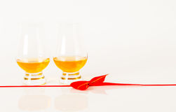 Set of single malt tasting glasses, single malt whisky in a glasses, white background, red bow. Exclusive set stock photography