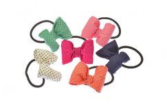 Set of six rubber hair scrunchies and rubber bands, of different colors and with colorful bows, isolated on white background.  royalty free stock image