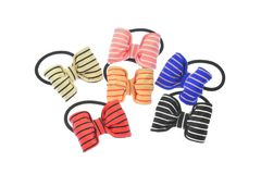 Set of six rubber hair scrunchies and rubber bands, of different colors and with colorful bows, isolated on white background.  royalty free stock photos
