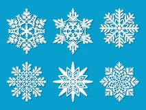 Set of six white paper cut out vector snowflakes on blue background.