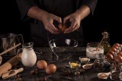 Set składniki i piekarniana ` s ręka roztrzaskujemy jajka w puchar odizolowywającego na czerni Obrazy Royalty Free