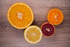 Set of sliced citrus fruits lemon , orange, grapefruit, tangerine  over wooden background. Top view. Stock Photo