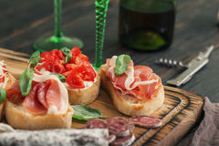 Set of small sandwiches with prosciutto, tomatoes, fresh basil Royalty Free Stock Image