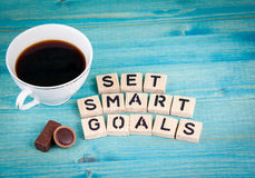 Set smart goals. Coffee mug and wooden letters on wooden background Royalty Free Stock Image