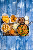 A set of snacks for beer. Chicken sticks in batter, cheese, pork ears, toasts, sauces and cabbage on a wooden board Stock Photography