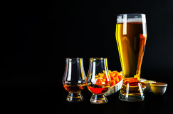 Set of snacks with different dips, single malt in a glass and pi. Nt of beer, crunchy snacks in a bowls, good food, black background royalty free stock photo