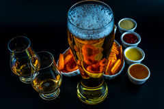 Set of snacks with different dips, single malt in a glass and pi. Nt of beer, crunchy snacks in a bowls, good food, black background stock image