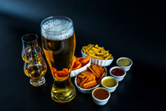 Set of snacks with different dips, single malt in a glass and pi. Nt of beer, crunchy snacks in a bowls, good food, black background stock photos