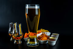 Set of snacks with different dips, single malt in a glass and pi. Nt of beer, crunchy snacks in a bowls, good food, black background royalty free stock photography