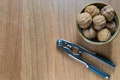 Set of some nuts and a nutcracker. On a wood background stock photo