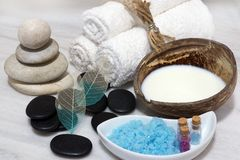 A set for Spa procedures with coconut milk rejuvenating milk, stones and blue bath salt is located on the white marble. Countertop Stock Images