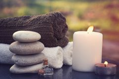 Set for spa procedures on the garden table, hot candles, towels and massage oil.  stock photos