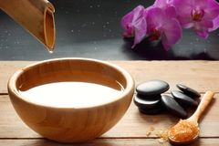 A set for spa procedures, hot massage stones, bath salts and flavored water collected from a bamboo stem into a bowl, orchid flowe. Rs in the background Royalty Free Stock Photo