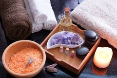 Set for spa procedures with salt of different colors, hot stones with aromatic oil and soft towels. Stock Image