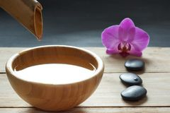 Set for spa procedures, stones for hot massage and flavored water, recruited from a bamboo stem into a bowl.  Stock Image