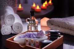 Set for spa procedures - stones for massage, oil, sea salt of violet and natural amethyst lies in a box. Moist towels Royalty Free Stock Photography