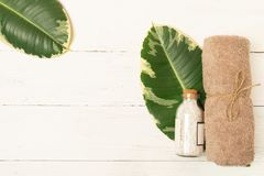 Set for spa treatments. Clean soft towels bath salts are stacked on leaf tropical green plant on a light background. royalty free stock images