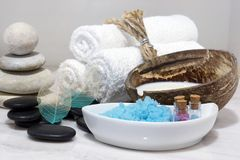 A set for Spa treatments with coconut milk, hot stones and blue bath salt is located on a white marble countertop. A set for Spa treatments with coconut milk Stock Image