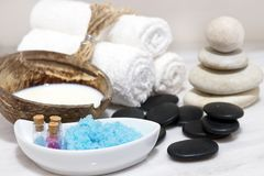 A set for Spa treatments with coconut milk, hot stones and blue bath salt is located on a white marble table. A set for Spa treatments with coconut milk, hot Stock Photo