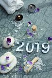 Set for spa treatments in 2019 on marble stone with candles, figures, bath salt and towels royalty free stock image
