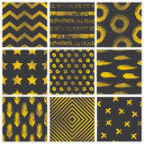 Set of spectacular patterns with gold hand drawn elements on black background. Stock Image