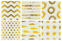 Set of spectacular patterns with gold hand drawn elements on light background. Royalty Free Stock Images
