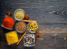 Set of spices on a dark brown textured wooden table - coriander Stock Photos
