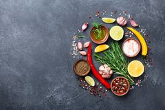 Set of spices and herbs on black stone table top view. Ingredients for cooking. Food background. Set of spices and herbs on black stone table from above stock photos