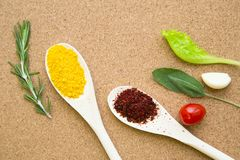 Set of spices and herbs on a corkwood. Cooking hot spicy meal. Dry red pepper and curcuma in wooden spoons fresh herbs and cherry tomato on a corkwood background Royalty Free Stock Image