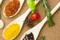 Set of spices and herbs on a corkwood. Cooking hot spicy meal. A set of three different spices in wooden spoons, fresh cherry tomatoe, garlic and rosemary Royalty Free Stock Images