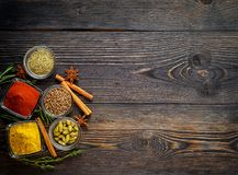 Set of spices and herbs on dark brown textured wooden table. Top Royalty Free Stock Images