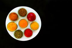 Set of spices and herbs on a white plate. Indian cuisine Pepper, salt, paprika, curry, basil, mustard, turmeric. View from stock photo