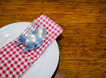 Set of spoon and fork on white plate. In restaurant Stock Image
