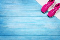 Set for sports activities on blue wooden background, top view. Fitness shoes over blue planks background. Sport shoes and accessories for sports activities on stock images