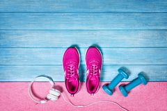Set for sports activities on blue wooden background, top view. Fitness shoes over blue planks background. Sport shoes and accessories for sports activities on royalty free stock images