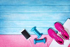 Set for sports activities on blue wooden background, top view. Fitness shoes over blue planks background. Sport shoes and accessories for sports activities on stock photography