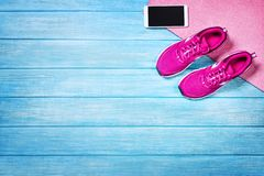 Set for sports activities on blue wooden background, top view. Fitness shoes over blue planks background. Sport shoes and accessories for sports activities on royalty free stock photo